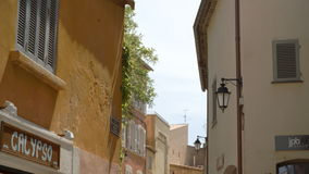 Old and narrow alleyway in St Tropez. A tilting down shot of yellow brick european buildings to the tourists walking in the old and narrow alleyway stock video