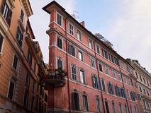 Old narrow dirty pink residential building with round balcony. Rome, Italy. Old narrow street and unusual old narrow dirty pink residential building with round Stock Image