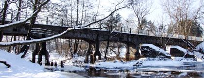 Old narrow-gauge railway bridge over Swider river. Old narrow gauge railway bridge over frozen Swider river in Jozefow. Covered with snow. Photo taken in winter Stock Photos