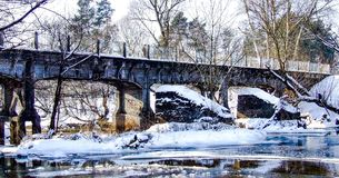 Old narrow-gauge railway bridge over Swider river. Old narrow gauge railway bridge over frozen Swider river in Jozefow. Covered with snow. Photo taken in winter Royalty Free Stock Photos