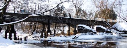Old narrow gauged railroad bridge in Jozefow near Warsaw. Bridge over frozen Swider river. Winter scenery, all covered with snow. Photo in Facebook background Royalty Free Stock Images
