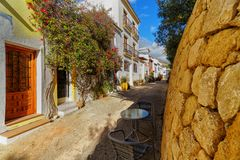 Old and narrow mediterranean street with table and chairs royalty free stock image