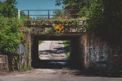 Graffiti Covered Railroad Underpass. Old and narrow railroad underpass covered with graffiti and ivy leaves, LaPorte, Indiana stock image