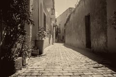 Old Narrow Street in Birkirkara, Malta. A typical old narrow street in Birkirkara, Malta featuring old houses in sepia and monochrome stock photo