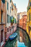 The old narrow street with a boat in Venice. Italy. Traditional Venetian street is a water canal. Boats are the main transport in Venice Royalty Free Stock Image