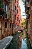 The old narrow street with a boats in Venice. Italy. Traditional Venetian street is a water canal. Boats are the main transport in Venice Royalty Free Stock Image