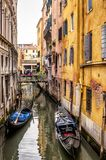 Old narrow street with gondolas in Venice. The old narrow street with gondolas in Venice, Italy. Traditional Venetian street is a water canal. Gondola is the Royalty Free Stock Photos