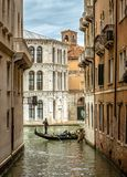 Old narrow street with lone gondola in Venice, Italy. Venice view, Italy. Old narrow street with lone gondola in the distance. Romantic water trip across vintage royalty free stock images