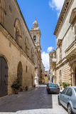 Old Narrow Street of Mdina with Carmelite Church Bell Tower - Mdina, Malta. Old Narrow Street of Mdina with Carmelite Church Bell Tower in Mdina, Malta Stock Photos