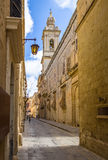 Old Narrow Street of Mdina with Carmelite Church Bell Tower - Mdina, Malta. Old Narrow Street of Mdina with Carmelite Church Bell Tower in Mdina, Malta Stock Photo