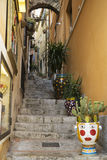 Old narrow street with staircase in Taormina on Sicily. With plants and cactuses in decorated flowerpots Stock Photo