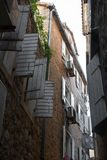The old narrow street, the view upstairs. Open window shutters stock image
