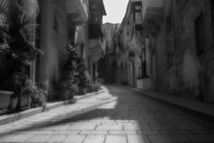 Old Narrow Streets in Birgu Malta. A historical old narrow street in Birgu, Malta in monochrome Stock Photos