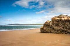 Old natural rock formation on deserted beach Stock Photo