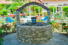 Old natural vintage stone will with pail standing in outdoor spa tropical garden grounds Royalty Free Stock Photo