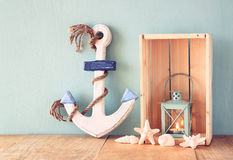 Old nautical wood anchor, lantern and shells on wooden table over wooden aqua background Royalty Free Stock Image