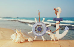 Old Nautical Wood Wheel, Anchor And Shells On Wooden Table Over Sea Background.