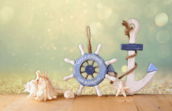 Old nautical wood wheel, anchor and shells on wooden table over abstract glitter background Royalty Free Stock Photography