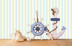 Old nautical wood wheel, anchor and shells on wooden table over retro background. Stock Photo