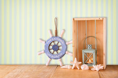 Old nautical wood wheel, anchor and shells on wooden table over retro background Stock Photos