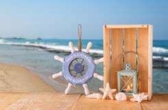 Old nautical wood wheel, anchor and shells on wooden table over sea background Stock Photography