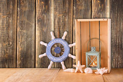 Old nautical wood wheel, anchor and shells on wooden table over wooden background Royalty Free Stock Photography
