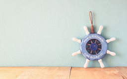 Old nautical wood wheel, anchor and shells on wooden table over wooden background. vintage filtered image Stock Photo