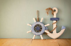 Old nautical wood wheel and anchor on wooden table over wooden aqua background Stock Photo