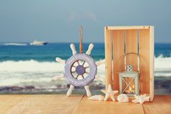 Old nautical wood wheel and shells on wooden table over sea background. Stock Images