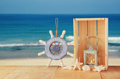 Old nautical wood wheel and shells on wooden table over sea background. Royalty Free Stock Image
