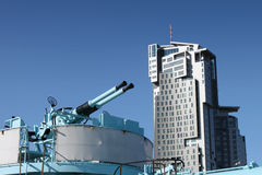 Old naval guns against modern building. Stock Photo