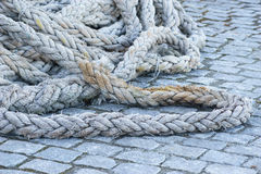 Old naval rigging rope. Thick old naval rigging rope tangled in knots on cobblestone pier, selective focus Royalty Free Stock Photography