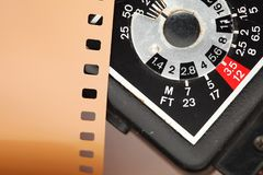 Old negative filmstrip. The old and dirty negative filmstrip and speed light dial panel represent the photography and camera support equipment concept related Royalty Free Stock Photo