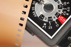 Old negative filmstrip. The old and dirty negative filmstrip and speed light dial panel represent the photography and camera support equipment concept related Stock Images