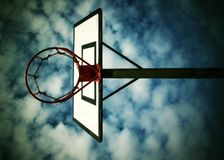 Old neglect basketball backboard with rusty hoop above street court. Blue cloudy sky in bckground. Retro filter Stock Photography