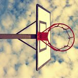 Old neglect basketball backboard with rusty hoop above street court. Blue cloudy sky in bckground. Retro filter Royalty Free Stock Images