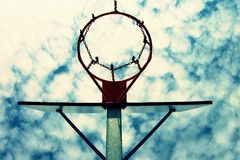 Old neglect basketball backboard with rusty hoop above street court. Blue cloudy sky in bckground. Retro filter Stock Images