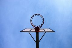 Old neglect basketball backboard with rusty hoop above street court. Blue sky Royalty Free Stock Photography