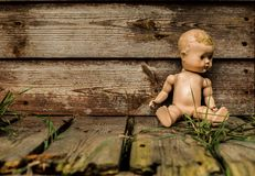 Old Neglected Doll In Front Of A Derelict Shed. Stock Photo