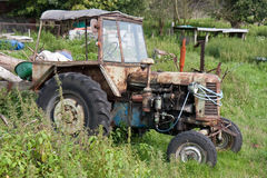 Old neglected tractor. Between the weed at a farmyard stock photography