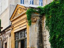 Old Neoclassical Bucharest House, Romania. Detail of an old neoclassical style stone Bucharest house with extensive green ivy, Romania royalty free stock photos