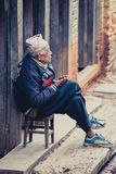 Old Nepalese man sitting in front of his home in Nepal Royalty Free Stock Photo