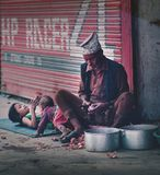 Old Nepali Man Peeling Red Onions Beside Two of His Grand Childr. En at Thamel Street Editorial Royalty Free Stock Photography