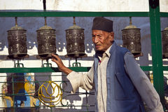 Old nepali man rotating buddhist prayer wheels in Nepal Royalty Free Stock Photo