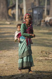 Old nepali woman carrying a young boy Stock Photography