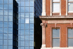 Old and new. Two neighboring buildings detail - modern structural glazing confronted to traditional neoclassical elevation Stock Photography