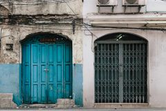 Old and New building with doors in colors in Bangkok. Old building with blue door next to new building with steel door in Bangkok Royalty Free Stock Image
