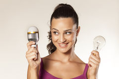Old and new bulb. Young smiling girl holds in her hands the old and the new generation of light bulbs royalty free stock photo