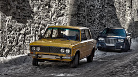 Old and new car. A contrasty photo of an old yellow Russian and new dark American passenger vehicles parking next to huge curtain wall made of limestone Stock Photo