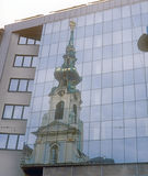 Old and new. Old church in Vienna is reflected in a modern glass facade Royalty Free Stock Photo